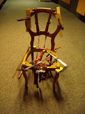 De lijmtangen houden de stoel bij elkaar zodat het kan drogen