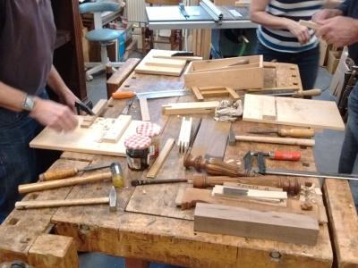 De werkbank ligt vol met hout waar aan gewerkt wordt